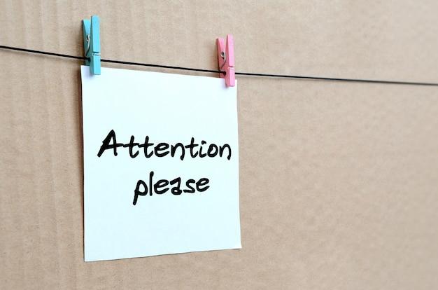 Aandacht aub. opmerking staat op een witte sticker die met een wasknijper aan een touw op een achtergrond van bruin karton hangt