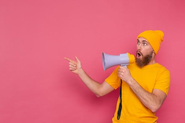 Aandacht! europese man met megafoon wijzende vinger naar links op roze achtergrond