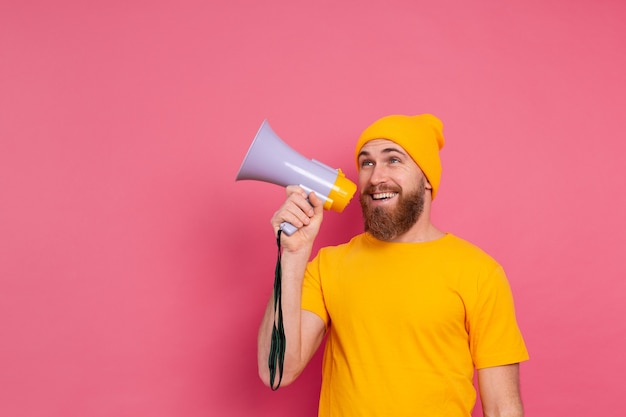 Aandacht! europese man schreeuwen in megafoon op roze achtergrond