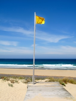 Aandacht, gele vlag op het strand