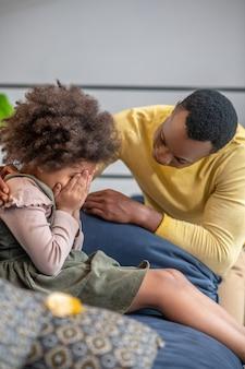 Aandacht. klein afrikaans-amerikaans meisje verbergt gezicht zittend op de bank en attente vader in gele trui die zijn schouders aanraakt