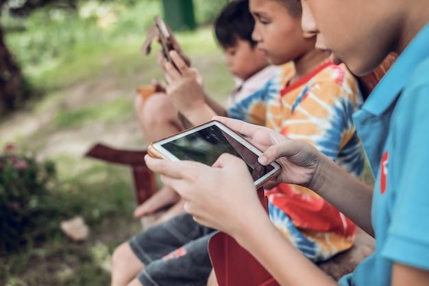 Aandacht van de jongens voor het spelen van tablet in groep