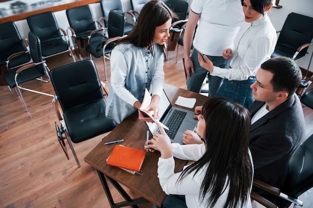 Aandacht voor details. mensen uit het bedrijfsleven en manager werken aan hun nieuwe project in de klas