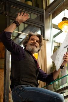 Aandacht vragen. vrolijke bebaarde man met een cafémenu die zijn hand opsteekt en een ober roept.