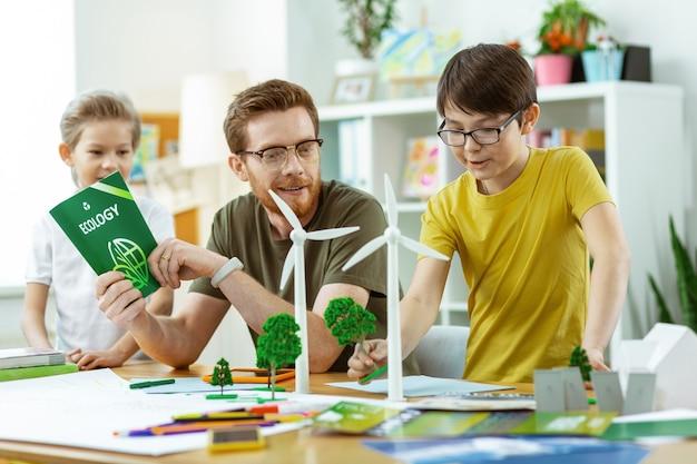 Aandachtig inspecteren. betrokken donkerharige kleine jongen met heldere bril die modellen aanraakt op de tafel van hun leraar