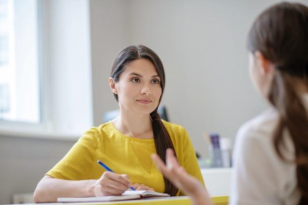 Aandachtig luisteren jonge mooie vrouw psycholoog met pen in de hand zittend aan tafel en meisje met haar rug naar de camera