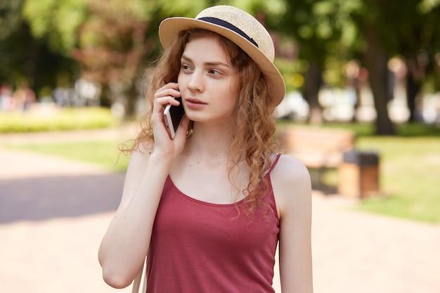 Aandachtig slank mooi meisje dat langs parkstraat loopt, haar smartphone dichtbij oor houdt, die over mobiele telefoon spreekt, ernstig gesprek heeft, aandachtig opzij kijkt, genietend van haar vrije tijd.