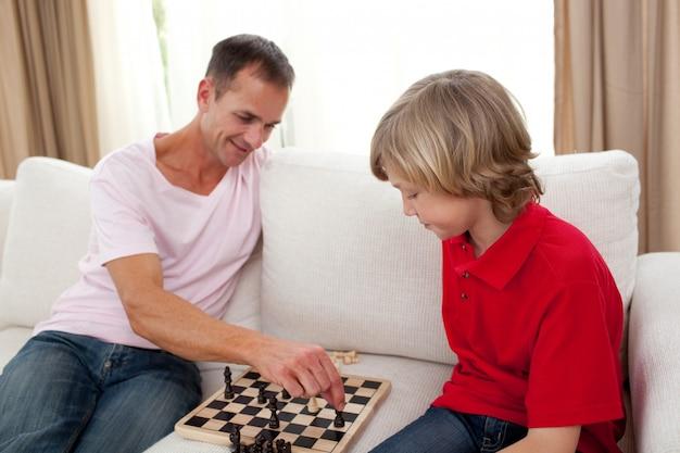 Aandachtig vader het spelen schaak met zijn zoon