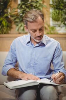 Aandachtige arts die in organisator schrijft
