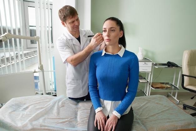 Aandachtige arts die ooronderzoek van mooie vrouw doet