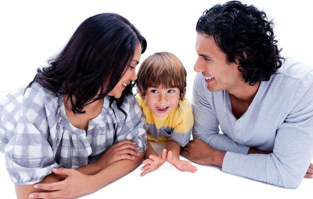 Aandachtige jonge ouders met hun zoon die op de vloer ligt