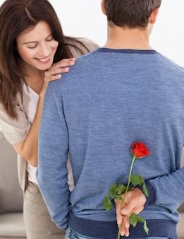 Aandachtige man die een bloem achter zijn rug voor zijn impatiente vriendin verbergt