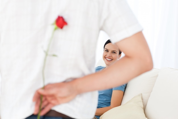 Aandachtige man die een bloem achter zijn rug voor zijn vriendin hidding