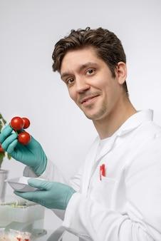 Aandachtige mannelijke bioloog of tech met tomatensteekproef