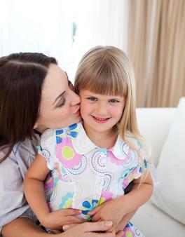 Aandachtige moeder die haar meisje kust