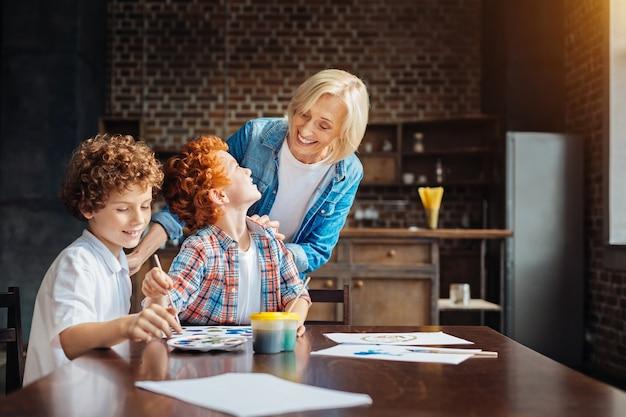 Aandachtige oudere dame raakt de schouders van haar kleinzonen aan terwijl ze kijkt hoe ze schilderen en met haar praten aan een tafel.