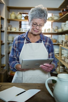 Aandachtige vrouwelijke pottenbakker die digitale tablet gebruiken