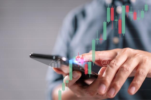 Aandelenhandelconcept met persoon die een smartphone vasthoudt