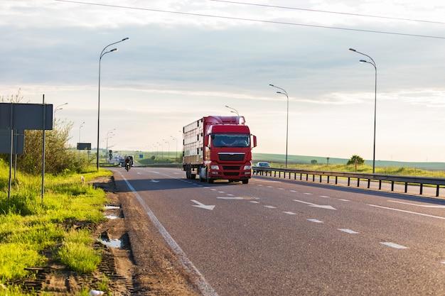 Aangekomen witte vrachtwagen op de weg in een landelijk landschap bij zonsondergang