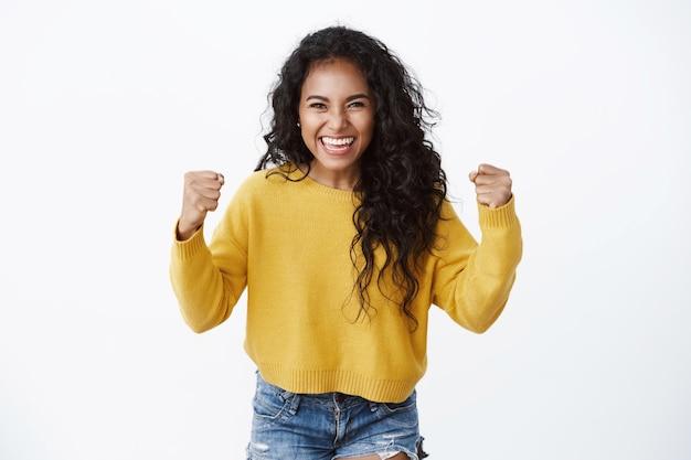 Aangemoedigde en gemotiveerde schattige vrouw in gele trui die handen opsteekt, vuistpomp van geluk, glimlachend goed nieuws horen, overwinning vieren, enorme weddenschap winnen, witte muur