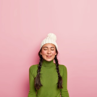 Aangenaam donkerharig meisje houdt de ogen gesloten, denkt aan een prettige ontmoeting met een vriend, draagt een witte hoed en een groene coltrui, staat tegen een roze muur