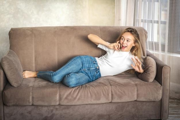 Aangenaam gesprek met een vriend. aantrekkelijke glimlachende jonge blonde vrouw die op celtelefoon spreekt terwijl thuis het liggen op de beige bank. technologie, communicatie en gezelligheidsconcept