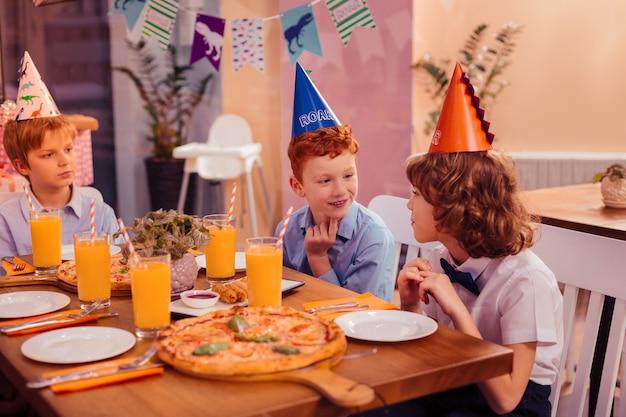 Aangenaam gesprek. vrolijke roodharige feestvarken die glimlach op zijn gezicht houdt terwijl hij naar zijn broer kijkt