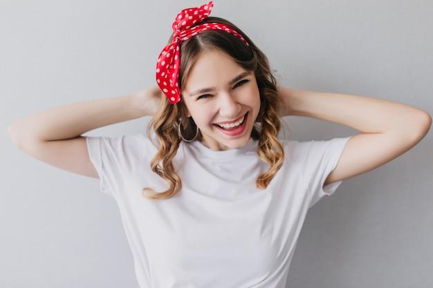 Aangenaam kaukasisch meisje in het witte t-shirt poseren. indoor portret van lachen prachtige vrouw met krullend kapsel.