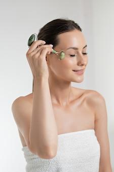 Aangenaam kaukasisch model met natuurlijke schoonheid die huidprocedures doet met jaderoller. jonge vrouw met bruin haar gewikkeld in een handdoek. geïsoleerd over witte studioachtergrond.