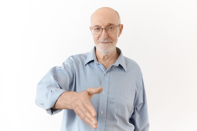 Aangenaam kennis te maken. geïsoleerde shot van elegante formeel geklede oudere man met witte baard die handpalm reikt en je hand gaat schudden als teken van begroeting. lichaamstaal, tekens en gebaren