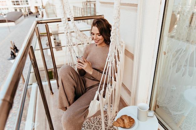 Aangenaam meisje sms-bericht tijdens de lunch op balkon. elegante jonge vrouw zit op terras met croissant en thee.