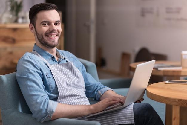 Aangenaam moment. positieve jonge knappe man glimlachend en bezig met laptop zittend in een fauteuil.