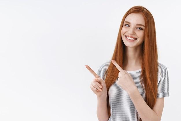 Aangenaam mooi roodharig jong meisje blauwe ogen met zomers gestreept t-shirt wijzend in de linkerbovenhoek wijsvingers presenteren geweldige productadvertentie die gelukkig glimlacht, witte muur