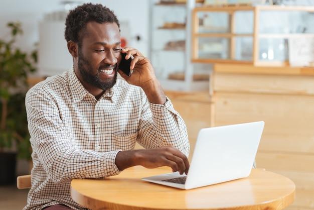 Aangenaam nieuws. vrolijke knappe man zit aan de tafel in het koffiehuis, ontvangt goed nieuws over werk aan de telefoon terwijl hij met één hand op laptop typt