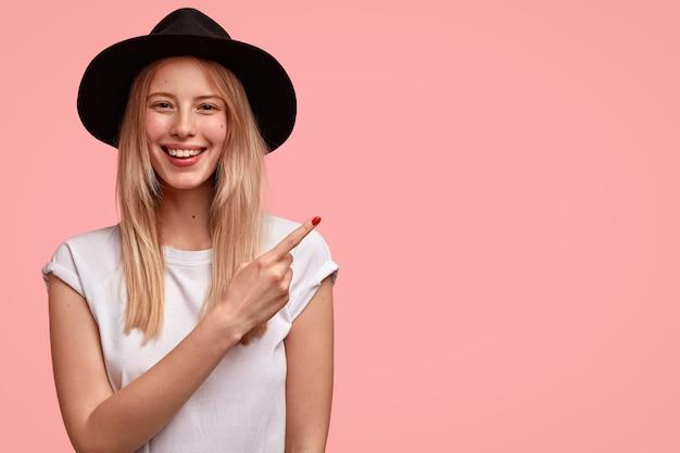 Aangenaam ogende europese vrouw met een aantrekkelijk uiterlijk, draagt hoed en casual t-shirt, wijst opzij