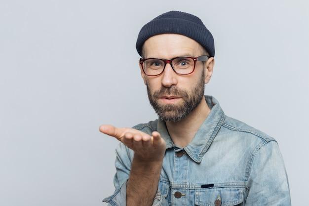 Aangenaam ogende jonge bebaarde man met snor, draagt modieuze bril, zwarte hoed en denim shirt