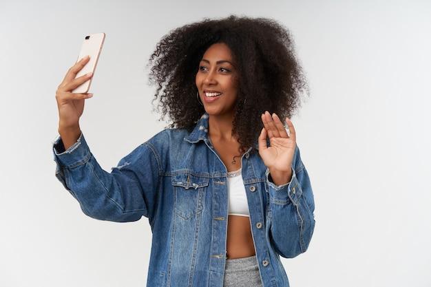 Aangenaam ogende jonge, krullende, donkere vrouw met videochat op haar mobiele telefoon en hand in hand in welkomstgebaar, oprecht glimlachend terwijl ze over witte muur poseert
