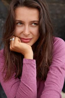 Aangenaam ogende jonge vrouw met een peinzende uitdrukking, heeft een aantrekkelijk uiterlijk