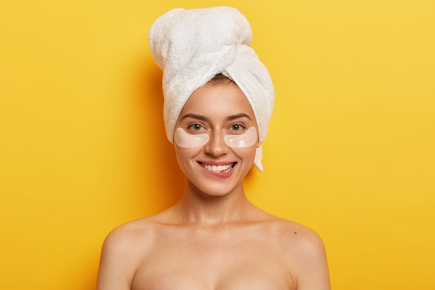Aangenaam ogende jonge vrouw staat shirtless binnenshuis, lacht positief, draagt onder ooglapjes, zachte handdoek op het hoofd