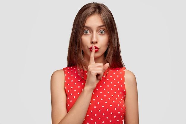 Aangenaam ogende langharige jonge vrouw draagt rode lippenstift, maakt een stil gebaar, vraagt niemand geheim