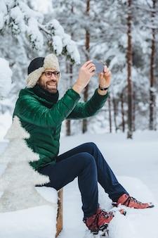 Aangenaam ogende man maakt foto met slimme telefoon