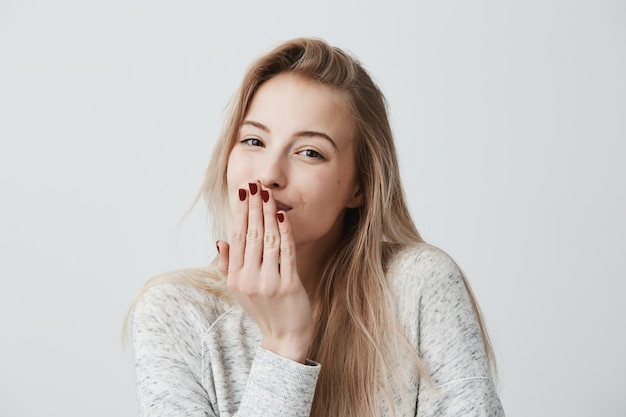 Aangenaam ogende mooie blonde vrouw met rode manicure blaast kus