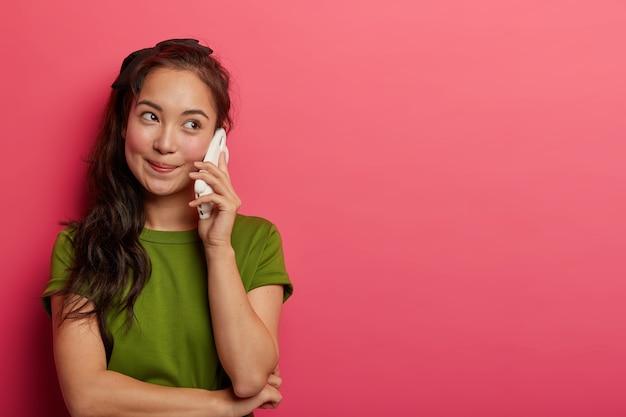 Aangenaam ogende natuurlijke brunette meisje houdt smartphone in de buurt van oor, geniet van leuke telefoongesprekken, kijkt opzij, draagt casual t-shirt, bespreekt iets interessants met vriend, geïsoleerd op roze muur