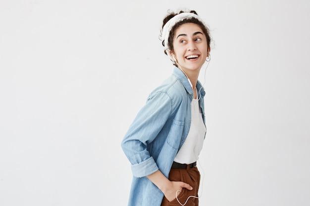 Aangenaam ogende vrolijke vrouw met golvend haar in knot, hand in zak houdend, mobiele telefoon gebruikt voor communicatie met vrienden of geliefde, luisterend naar aangename muziek, goed humeur.