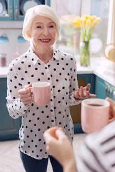 Aangenaam tijdverdrijf. charmante oudere vrouw met een kopje koffie en lacht naar haar dochter terwijl ze met haar praat in de keuken