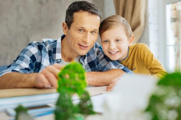 Aangenaam tijdverdrijf. vrolijke jongeman die naast zijn kleine zo zit en het miniatuurstadsmodel onderzoekt dat op de tafel staat, het zelf gemaakt te hebben