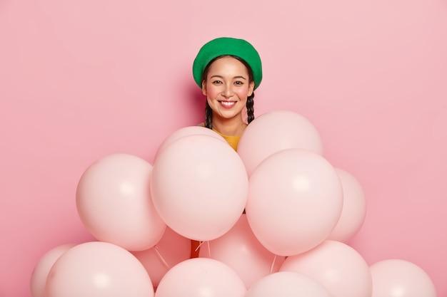 Aangenaam uitziend aziatisch vrouwelijk model draagt groene baret, staat in de buurt van veel ballonnen, vormt op roze achtergrond, viert verjaardag