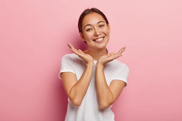 Aangenaam uitziend aziatisch vrouwelijk model glimlacht blij, spreidt de handpalmen in de buurt van het gezicht, drukt positieve emoties uit, draagt een wit t-shirt, heeft een aantrekkelijk uiterlijk, een gezonde huid, geïsoleerd op een roze muur