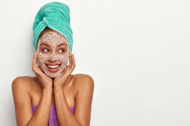 Aangenaam uitziend model met een donkere huid houdt de handen op het gezicht, brengt een scrubmasker aan, witte zeezoutkorrels, kijkt opzij, in een goed humeur