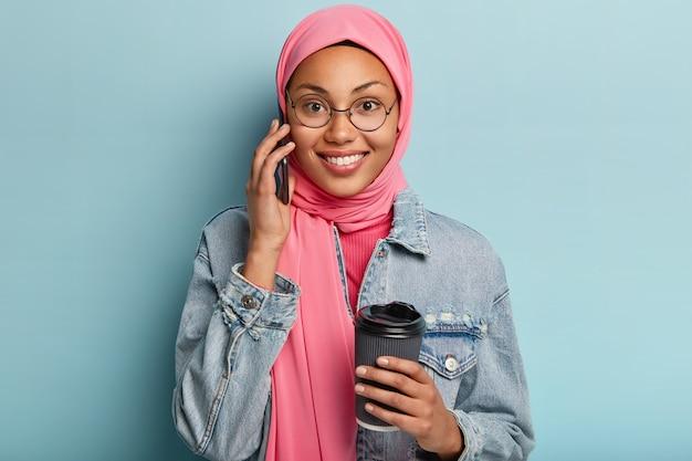 Aangenaam uitziende blije etnische vrouw heeft een leuk informeel gesprek, geniet van een ochtendkoffiepauze, houdt een wegwerpbeker vast, draagt een ronde bril, bedekt het hoofd met een hijab. vrije tijd concept